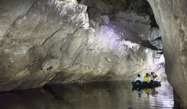 Exploring Barton Creek Cave in Cayo District, Belize by canoe. Guides offer trips into the first kilometer of this cave, where ledges hold Mayan pottery shards and human remains dating from 200 to 900 AD.