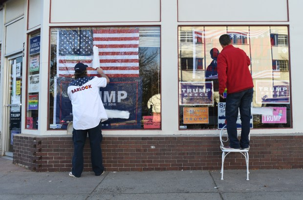 Stephen Barlock, left, and Jeffrey Eggemeyer, both Denver Co-Chairs of the Trump Campaign Colorado, work on clean off vandalism outside Trump's Denver headquarters