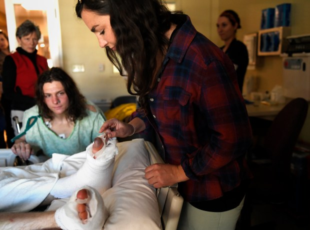 Older sister Heather Hendricks reaches in carefully to touch the frostbitten toe of her younger brother Tommy Hendricks, 18, while his climbing partner Matt Smith, 17, watches as they tell stories of their adventure during their recovery at University of Colorado Burn Center on Nov. 25, 2016, in Aurora.