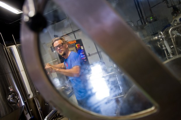 Nate Luebbe takes a sample from the kettle while brewing at Upslope Brewing Company in Boulder.