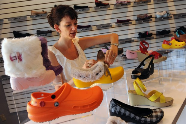 A Crocs employee organizes the shoe display in the front entrance at the company's headquarters in this file photo.