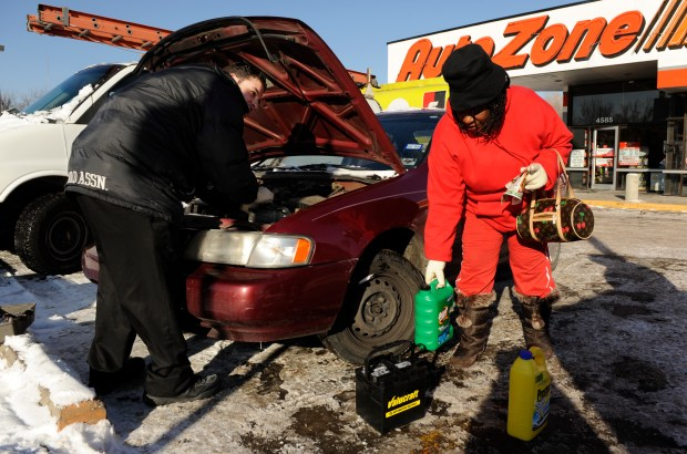 At the Auto Zone at 4585 E. Colfax, employee Jeremy Yara replaces the car battery for Emma Barrott, right, and her husband as Emma readies anti-freeze for the car ahead of sub-zero temperatures on Dec. 15, 2008.