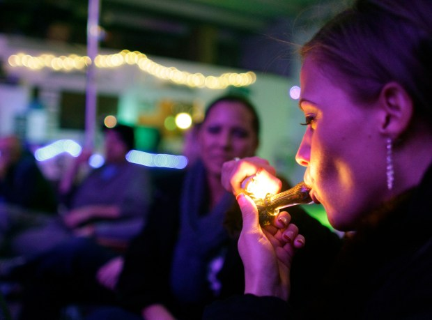 In this Dec. 31, 2012 file photo, Rachel Schaefer, of Denver, smokes marijuana on the official opening night of Club 64, a marijuana-specific social club, where a New Year's Eve party was held in Denver.