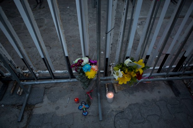 Flowers, candles, and a cross are placed outside barriers blocking the entrance to the Blue Parrot club, where several people were killed in early morning gunfire in Playa del Carmen, Mexico, Monday, Jan. 16, 2017. Deadly gunfire broke out in the crowded beachfront nightclub throbbing with electronic music before dawn on Monday, setting off a bloody stamped by screaming concertgoers at an international festival in this Caribbean resort.