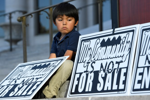 Giovanni Rodriguez, 5, sits next to signs during a press conference held on the steps of the Denver City and County building on Sept. 19, 2016 in Denver. The group holding the press conference, made up of city councilmen and women, local leaders and neighbors, are protesting the lack of affordable housing in lower income neighborhoods such as Swansea and Globeville. They are calling it a state of emergency for Denver families who are under threat of being involuntarily displaced due to gentrification pressures in areas such as Globeville, Elyria and Swansea.