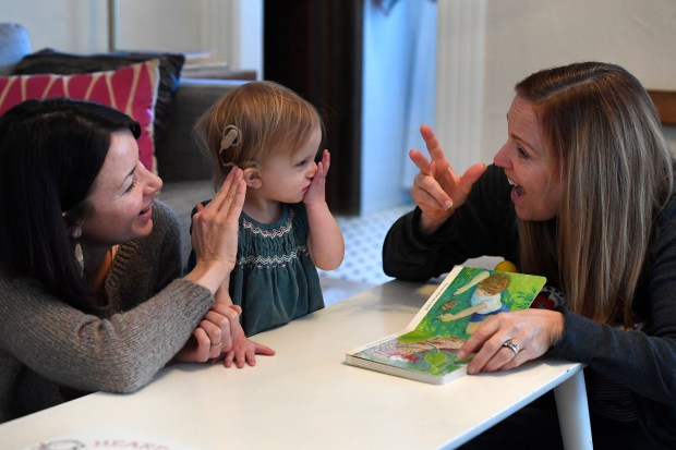 American Sign Language teacher Lori Fisk, right, works with 19 month old Anna Wiedel, middle, and her mother Megan, left, during a tutoring session at Anna's home on January 26, 2017 in Wheat Ridge, Colorado. Anna was born profoundly deaf as a result of an infection from CMV, a common virus that pregnant women are often under-educated about. It is estimated that, in reality, 20,000 to 40,000 babies in America are born with congenital CMV each year but arenÕt diagnosed because they appear healthy at birth or doctors mistake their symptoms for other diseases. Anna contracted CMV in-utero from her mother Megan not because the family traveled to another country, but because they have a toddler. CMV is spread most often through the saliva and urine of children under the age of 3 in some studies, it is present in 44 to 100% of toddlers at daycare centers, and they will go on to shed it for two years or longer.