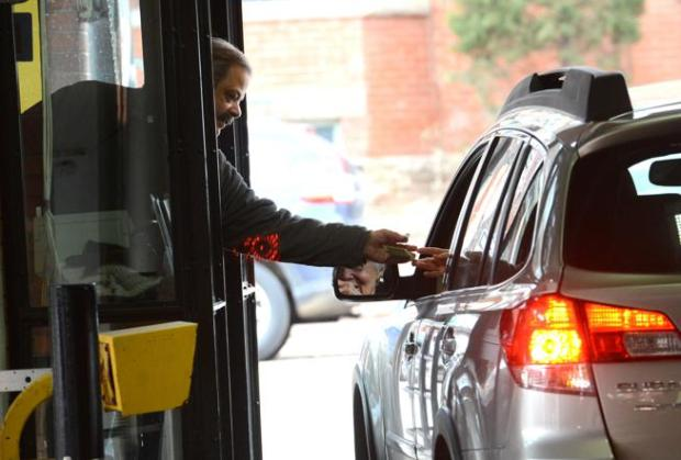 Paul Lepant makes change for a driver who parked at the 11th & Spruce Parking Garage on Thursday in Boulder.