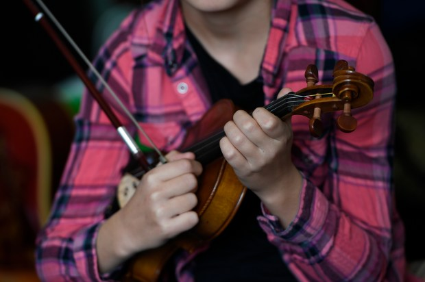 Fiddle student Wynn Rutberg, 10, tunes her fiddle as she prepares to play with her teacher Katie Glassman (not shown) at Glassman's home on Dec. 14, 2016 in Denver.
