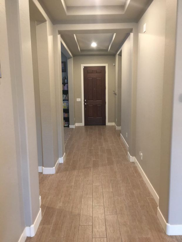 To turn a long corridor into an inviting entry, we defined the space by the door with entry furnishings, and let the rest of the hall serve as transition space.