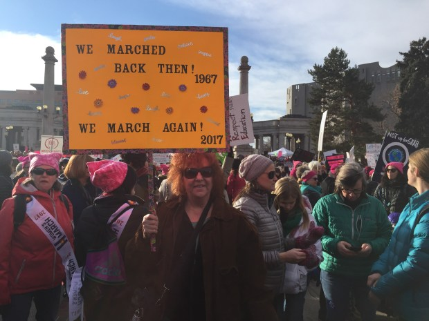 """Cat Delaney, 65 and of Denver, awaits the Women's March on Denver as she hold her sign, """"We marched back then! 1967 We march again! 2017."""""""