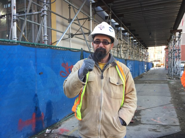 Caption: Jose Luis Valdez Sierra,42, watches the Women's March in Denver pass by his construction site alongside his coworkers.