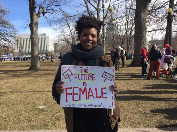 """Caption: Sam Casanova, 23 and of Denver, stands inside Civic Center Park shortly after the march and reflects while holding her sign that reads, """"The future is female."""""""