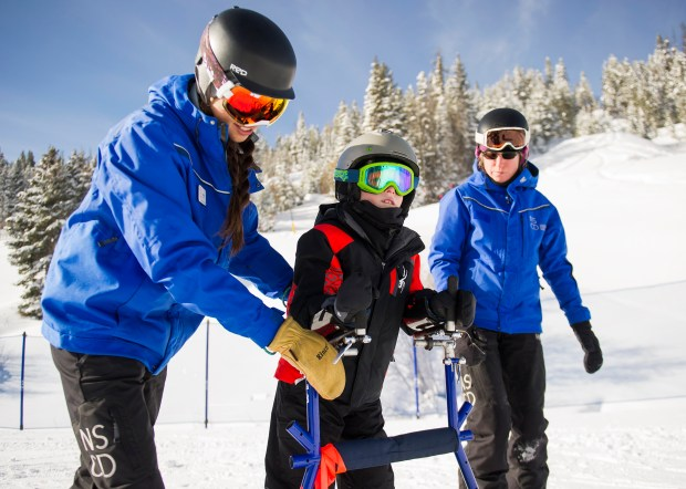 Luke Smith, 9, during his adaptive ski lesson with instructors Sarah Tey, left, and Maddie Reynolds, right, Jan. 7, 2017 on the Sorensen Park bunny hill at Winter Park.