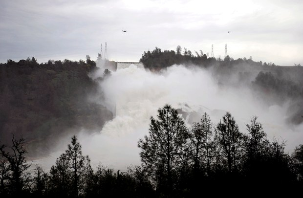 Water gushes down the Oroville Dam's main spillway on Wednesday in Oroville, Calif. The Oroville Reservoir is continuing to drain as state water officials scramble to reduce the lake's level ahead of impending storms.