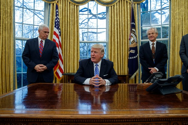 Vice President Mike Pence, left, and National Trade Council adviser Peter Navarro stand behind President Donald Trump before the signing of three executive orders on Jan. 23 at the White House.
