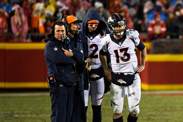 Denver Broncos head coach Gary Kubiak, offensive coordinator Rick Dennison, and quarterbacks Paxton Lynch and Trevor Siemian huddle during a timeout in the first half of the Broncos' game against the Kansas City Chiefs on Dec. 26.