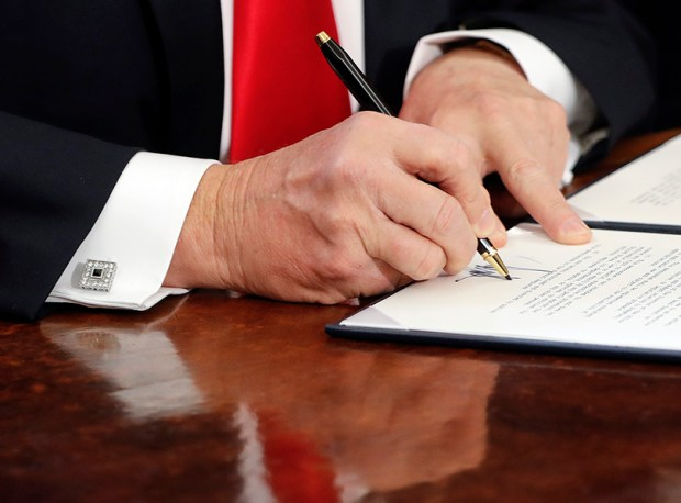 President Donald Trump signs an executive order at the White House on Feb. 3.