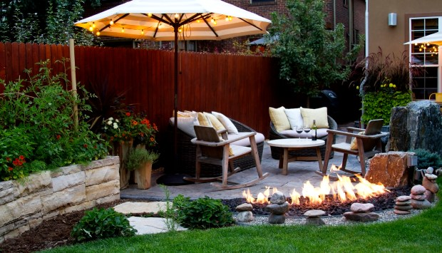 In this back yard, Environmental Designs filled the space between stepping stones leading to the raised patio with strawberries. The fire feature hugs the top of the paver patio.