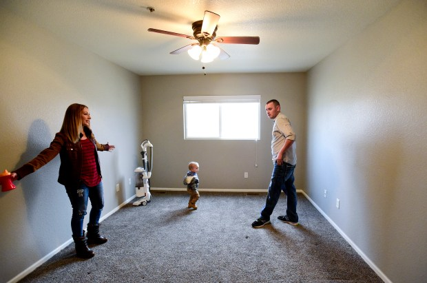 From left: Hallie Moran, Jackson Moran, 16 months, and Thomas Moran take a look at the master bedroom during a walk-through at the River Bend Town Homes