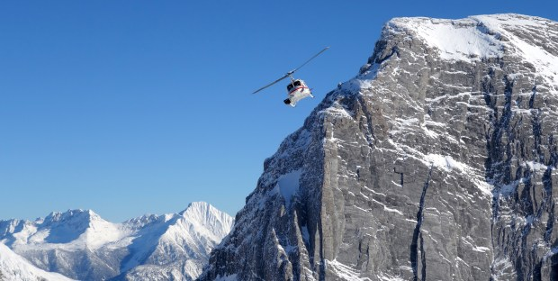 A helicopter operated by pioneer CMH Heli-Skiing hugs a powdery peak in British Columbia.