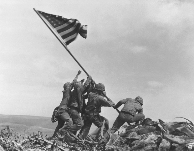 Feb. 23, 1945: U.S. Marines of the 28th Regiment, 5th Division, raise the American flag atop Mt. Suribachi, Iwo Jima. Strategically located only 660 miles from Tokyo, the Pacific island became the site of one of the bloodiest, most famous battles of World War II against Japan.