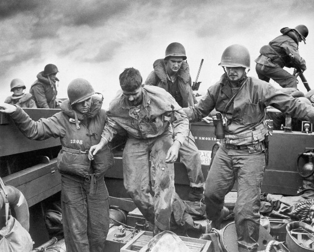 Feb. 28, 1945: Wounded when Japanese fire made a direct hit on an Amtrac, a Marine is transferred by Coast Guardsmen to a landing craft off the flaming shore of Iwo Jima, Japan on D-Day. After darting in with boatloads of Marines, a Coast Guard-manned landing craft ran back to sea with casualties to LST's, specially fitted as temporary hospital ships. Intense enemy fire exacted a heavy toll as the beachhead was established on the island fortress only 750 miles from Tokyo.