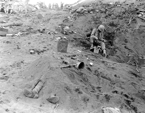 February 1945: The booted feet of a dead Japanese soldier, foreground, protrude from beneath a mound of earth on Iwo Jima during the American invasion of the Japanese Volcano Island stronghold in World War II. U.S. Marines can be seen nearby in foxholes.