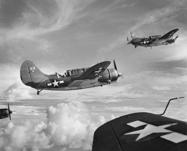 August 24, 1944: Curtiss Helldivers from the Fast Carrier Task Force 58 are seen midair on a mission over Saipan, in the Mariana Islands.
