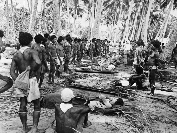 Jan. 21, 1943: Native stretcher bearers rest in the shade of a coconut grove as they and the wounded American soldiers they are carrying from the front lines at Buna, New Guinea take the opportunity to relax. The wounded are on their way to makeshift hospitals in the rear.