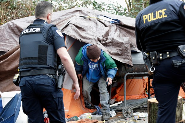 In this Feb. 16, 2017, photo, Leroy Henry, center, steps out of his tent in the woods to talk with police officer Kevin Davis, left, and Sgt. Mike Braley in Everett, Wash.