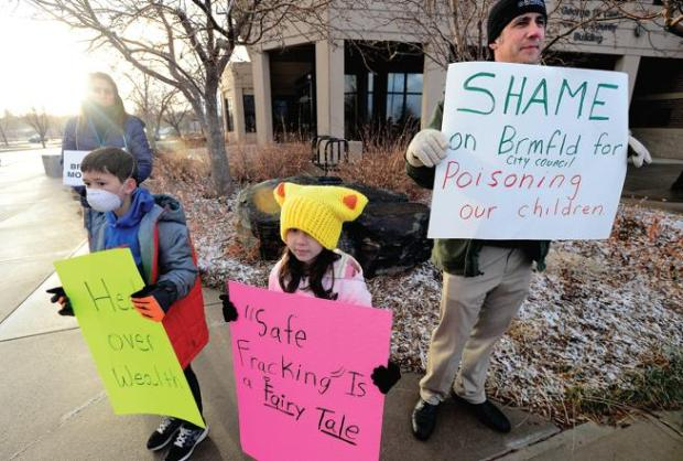 Broomfield resident George Jage protests with his children Kadin, 10, and Morgan, 7, outside the George Di Ciero City and County Building in Broomfield Tuesday evening in advance of the meeting to address oil and gas development in the city. (