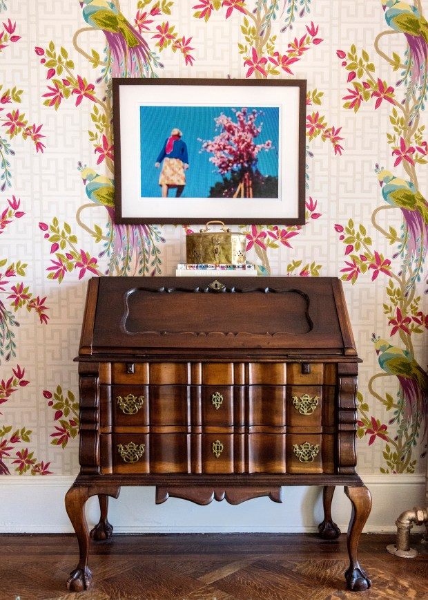 A tableau and artwork set off the colorful wallpaper in Elliott's entry hall.