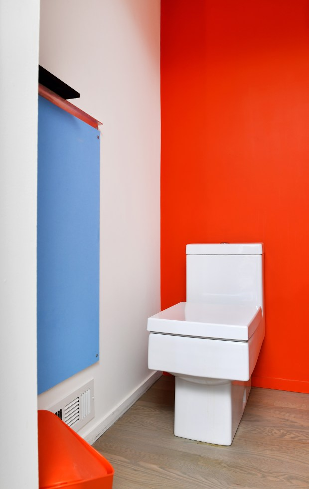 The powder room on the main level of the Coleman home has a pop of blue and one orange wall.