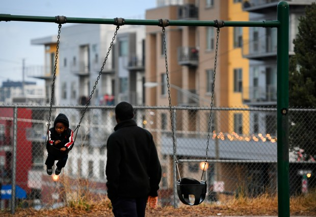 A man plays with his son at Hirshorn Park in Denver on Tuesday.