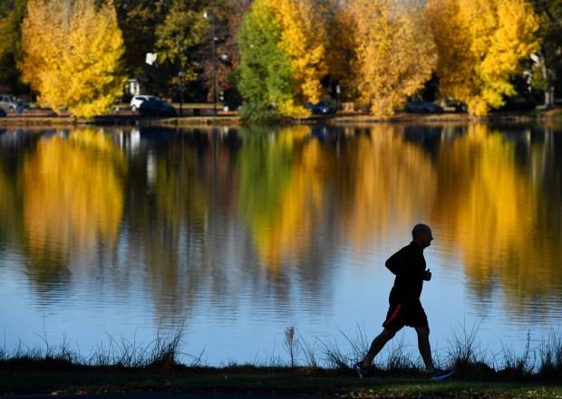 A jogger makes his way past Smith Lake in Washington Park.