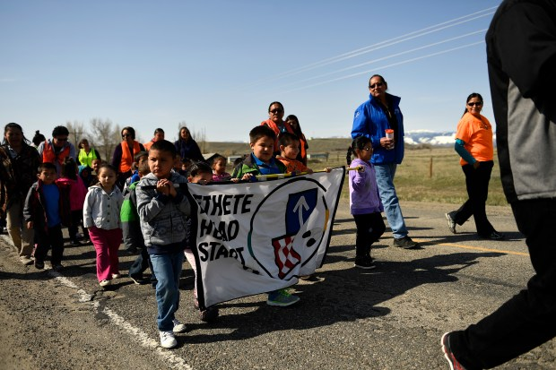 Marlin Spoonhunter, (2nd from right) president of the Wind River Tribal College, walks with Carrie White Antelope, (right) Family service manager of the Ethete Head Start, and pre-schoolers from the Ethete Head Start program during an honor walk for the Week of the Young Child on the Blue Sky Highway in the Wind River Indian Reservation April 10, 2017 in Ethete, Wyo.