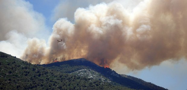 A photo of aircraft flying through a huge plume of smoke rising from a wildfire