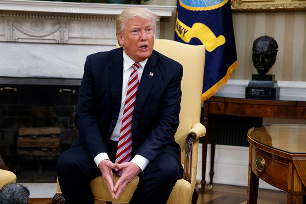 President Donald Trump talks to reporters during a meeting with former Secretary of State Henry Kissinger in the Oval Office of the White House on Wednesday.