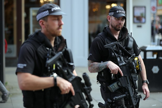 Armed police officers patrol St Ann's Square in Manchester, England, during a vigil on Wednesday. An explosion at Manchester Arena on Monday night killed 22 people and injured 59.