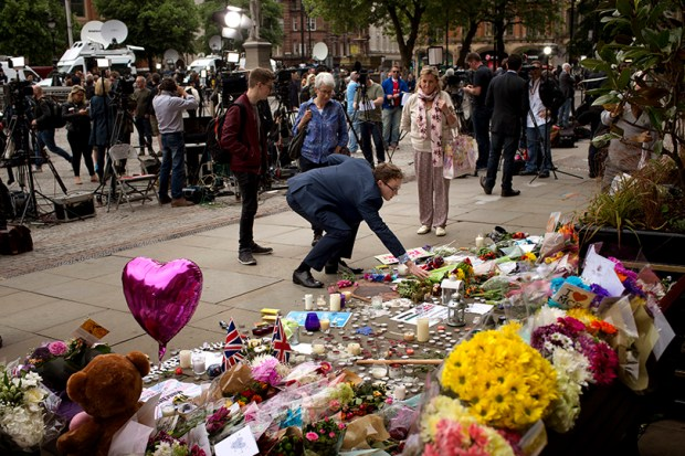 In a scene that has become familiar around the world, a man places flowers in Albert Square in Manchester, England,, on Wednesday, two days after a suicide attack at a concert killed 22 people.