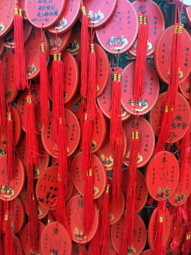 Hundreds of red hangings are tied to the outside of an incense burner at a temple on Mount Tai, China's most sacred mountain. People choose charms with their Chinese zodiac and write on them to pray for blessings or make a wish.