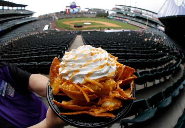 A bowl of apple pie nachos is shown at Coors Field in Denver, Saturday, May 6, 2017. The $6 bowl consists of cinnamon-covered nacho chips, apple pie filling and cheddar cheese, topped with whipped cream and then drizzled with caramel sauce. The concoction is rated at 740 calories. (AP Photo/David Zalubowski)