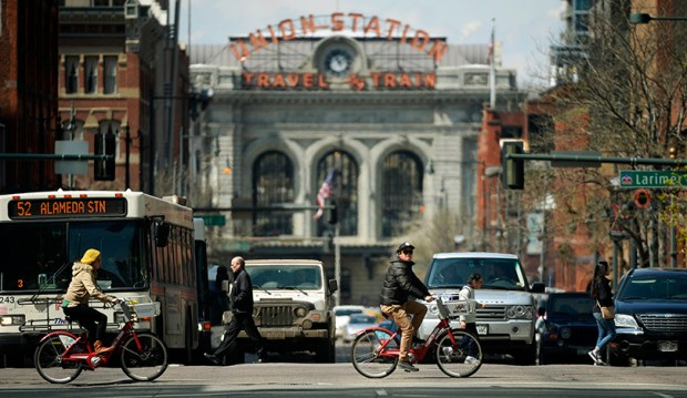 Two B-Cycle riders cross 17th Street as they ride along Lawrence Street near Union Station in Denver on April 3, 2015.