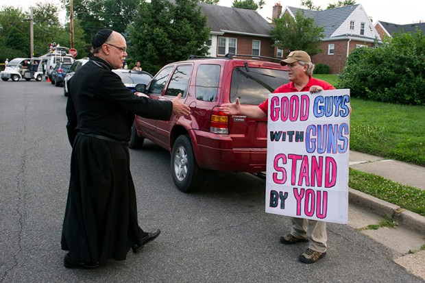 Father John Roddy shakes hands with Jeff Hulbert of Annapolis, Md., following a prayer service in Alexandria, Va., after a rifle-wielding attacker opened fire on Republican lawmakers at a congressional baseball practice, wounding House Rep. Steve Scalise of Louisiana and several others.