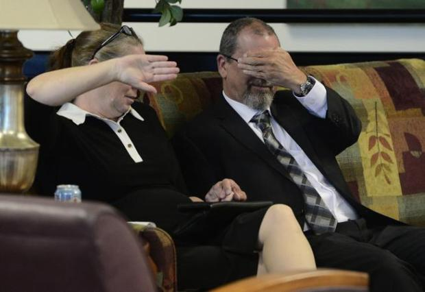 Jon Marc Barbour and a companion cover their faces as they wait for the afternoon session of his trial Monday at the Boulder County Justice Center.