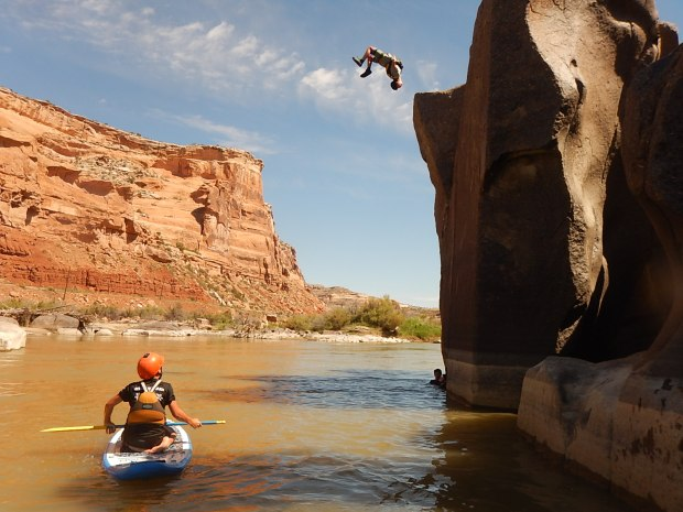 Dally Kellogg watches his older brother Brody throw a gainer off the cliffs along the Ruby-Horsethief section of the Colorado River in June 2016.