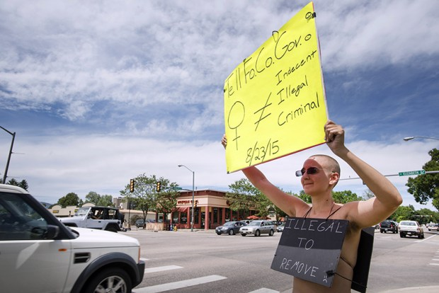 """A woman protests Fort Collins' indecency laws on Aug. 6, 2015. A federal judge earlier this year rejected claims by city leaders in Fort Collins that the female breast was """"a private part"""" and posed a threat to """"public sensibility."""""""