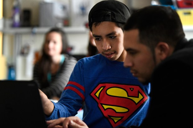 Josue Bonilla, 13, middle, works on the computer with his older brother Daniel, 23, right, who came to visit Josue in his Multi-Intensive class at Strive Prep on Dec. 20, 2016 in Denver.