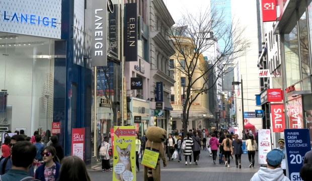 Pedestrians throng a street in Myeon-dong, one of Seoul's main shopping areas.