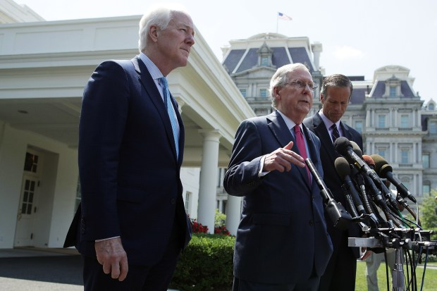 Senate Majority Leader Sen. Mitch McConnell speaks to members of the media as Sen. John Cornyn, left, and Sen. John Thune look on outside the West Wing of the White House after a lunch meeting with President Donald Trump to talk about health care on Wednesday.